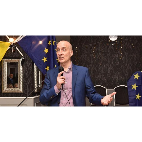 Lord Adonis in front of EU flags.